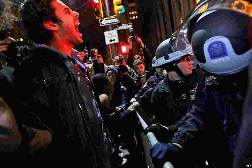 15 tháng 11: Một người biểu tình hét vào đám cảnh sát sau khi bị buộc phải rời công viên Zuccotti, nơi mà họ cắm trại lâu nay. (AP Photo/Mary Altaffer)