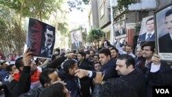 Membawa poster Presiden Bashar Assad, sekelompok warga Suriah melakukan aksi protes di luar Kedubes Suriah di Kairo pekan ini.