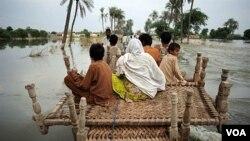 Penduduk desa Pakistan menyeberangi banjir di daerah Baseera, Pakistan, 24 Agustus 2010.