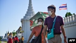 Dua wisatawan mengenakan masker saat mengunjungi Istana Raja di Bangkok, Thailand hari Senin (27/1).