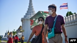People walk with face masks outside the Grand Palace in Bangkok on January 27, 2020. - Thailand has detected eight Coronavirus cases so far -- three of whom are receiving treatment in hospital and five of whom have been discharged, according to a statemen