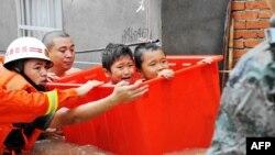 Des secouristes évacuent des enfants suite aux inondations causées par le typhon Megi à Ningde, dans la province du Fujian, dans l'est du pays, le 28 septembre 2016.