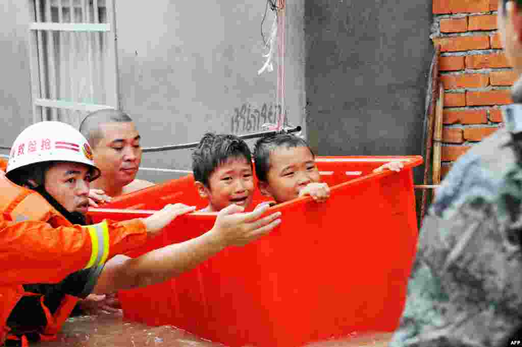 Rescuers evacuate flood-affected children in Ningde, eastern China's Fujian province. Typhoon Megi smashed into the Chinese mainland, killing one person, after leaving a trail of destruction and four people dead in Taiwan.