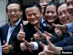 """Alibaba Group Holding Ltd founder Jack Ma (2nd L) poses as he arrives at the New York Stock Exchange for his company's initial public offering (IPO) under the ticker """"BABA"""" in New York Sept. 19, 2014."""