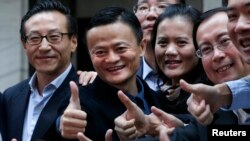 "Alibaba Group Holding Ltd founder Jack Ma (2nd L) poses as he arrives at the New York Stock Exchange for his company's initial public offering (IPO) under the ticker ""BABA"" in New York Sept. 19, 2014."