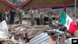 Soldiers remove debris from a partly collapsed municipal building felled by a massive earthquake in Juchitan, Oaxaca state, Mexico, Friday, Sept. 8, 2017. One of the most powerful earthquakes ever to strike Mexico has hit off its southern Pacific coast, k