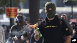 A protester looks at a petrol bomb before throwing it at Athens' main Syntagma Square, during violent demonstrations, October. 20, 2011.