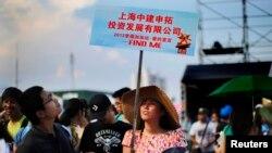 Seorang perempuan memegang papan dalam acara pencarian jodoh di pantai Jinshan, selatan Shanghai (20/7).