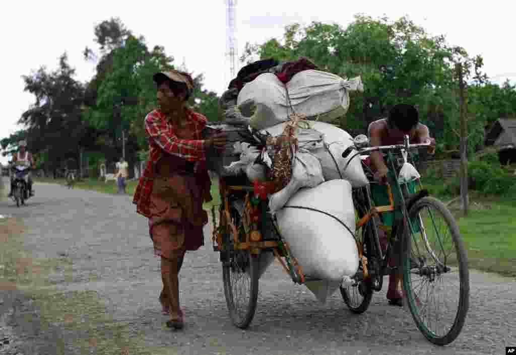 Cư dân đẩy một chiếc xe xích lô chở đồ đạc của họ trong một ngôi làng ở Sittwe, nơi bạo động giáo phái đang tác động đến người dân địa phương, ngày 11/6/2012