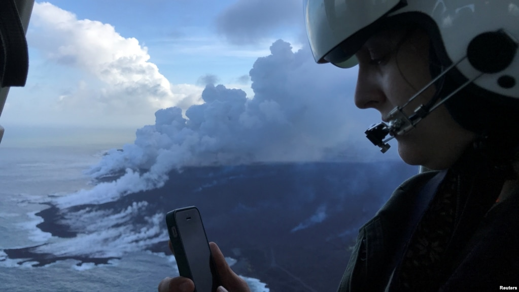 Dr. Jessica Ball of USGS, a geologist and volcanologist who does research at the US Geological Survey, is updating Hawaiian Volcano Observatory scientists on the ground during a helicopter overflight of the ocean entry of the fissure 8 lava flow where a laze (lava haze) plume is visible over the active parts of the flow margin near Kapoho, Hawaii, June 8, 2018.