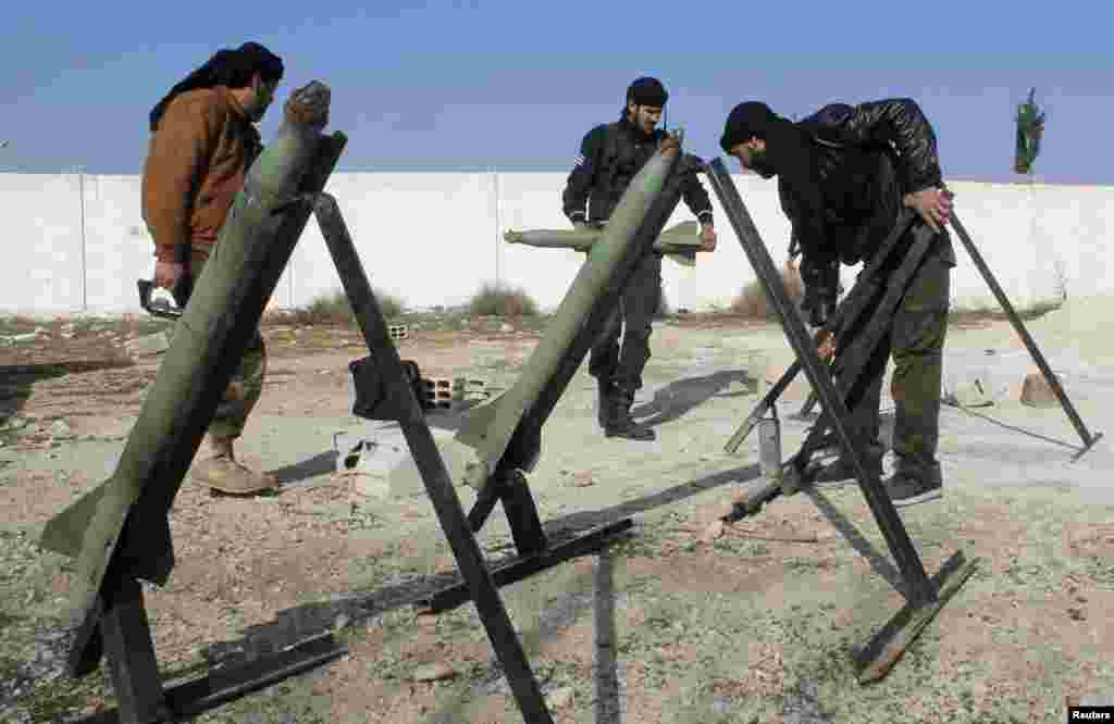 Fighters from the Free Syrian Army's Saif al-Umayyad brigade prepare rockets to be launched towards forces loyal to Syria's President Bashar al-Assad in the eastern Damascus suburb of Ghouta, Jan. 16, 2014.