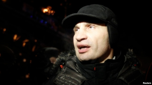 Heavyweight boxing champion and Ukrainian Democratic Alliance for Reform party leader Vitaly Klitschko walks past a riot police line in Kyiv, Dec. 11, 2013.