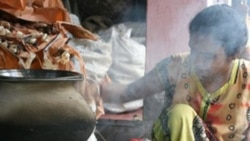 Smoke rises as an Indian woman cooks a mid-day meal on a traditional oven in Calcutta in 2007