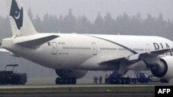 Hai cảnh sát chống khủng bố (giữa) dẫn một trong các hành khách đi khi chiếc Boeing 777 của hãng hàng không Pakistan di tản hành khách khỏi máy bay tại phi trường Stockholm, ngày 25 tháng 9, 2010
