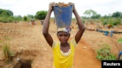 Une femme cherche de l'or après la découverte d'une nouvelle mine trouvée dans une ferme de cacao près de la ville de Bouafle, dans l'ouest de la Côte d'Ivoire, le 20 mars 2014.