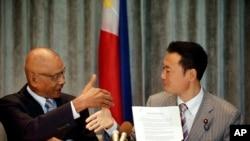 菲律賓眾議員比亞松(左)和日本代表團團長、在野的日本創新黨領袖中田宏在簽署一項推動海上法治的非正式協議後握手。