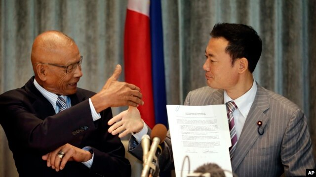Philippine Congressman Rodolfo Biazon, left, Chair of the House Committee on National Defense, and Hiroshi Nakada, Head of delegation of the Japanese opposition Party for Future Generations, shake hands shortly after signing a non-binding documents to rea