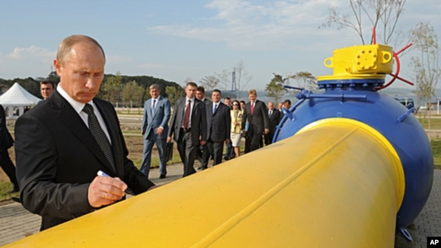 Russia's Prime Minister Vladimir Putin signs an autograph on a natural gas pipeline Sakhalin-Khabarovsk-Vladivostok in the Russian Far East city of Vladivostok during the pipeline's launch ceremony, September 8, 2011.