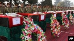 Anggota pasukan kehormatan berdiri tegak di dekat peti jenazah tentara Afghanistan korban serangan Taliban, dalam upacara pemakaman di Kabul, Afghanistan (24/2).