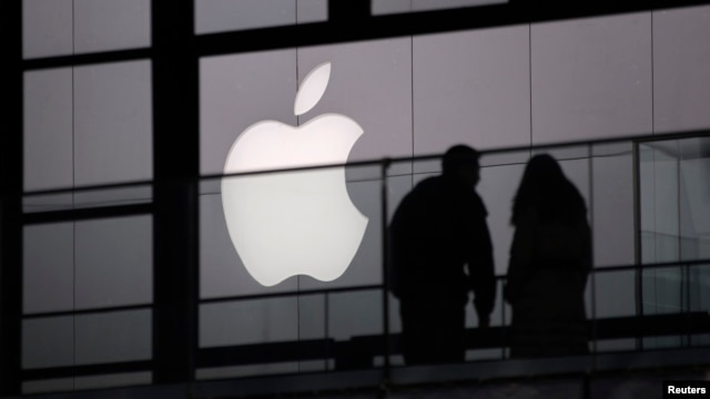 FILE - People walk past the Apple logo near an Apple Store at a shopping area in central Beijing, February 19, 2013.