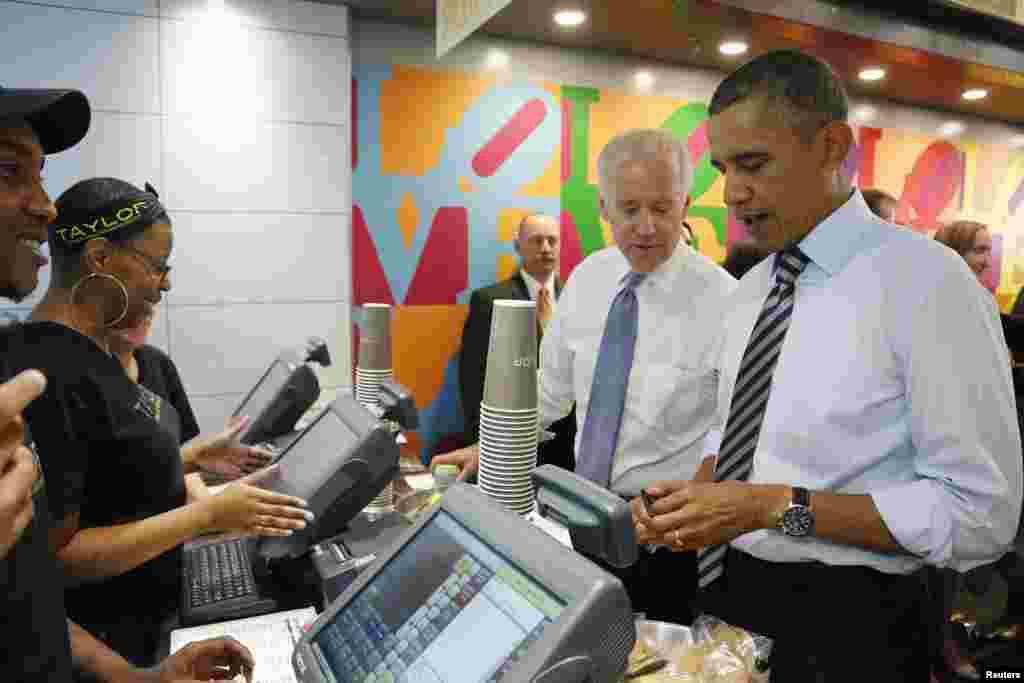 奥巴马总统(右)在华盛顿白宫附近的三明治店打开钱包为自己和拜登副总统(右二)买午饭