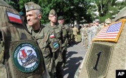 FILE - Polish Army and U.S. Army soldiers attend the opening ceremony of the Anaconda-16 military exercise, in Warsaw, Poland, June 6, 2016.