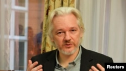 FILE - WikiLeaks founder Julian Assange gestures during a news conference at the Ecuadorian embassy in central London, August 18, 2014.