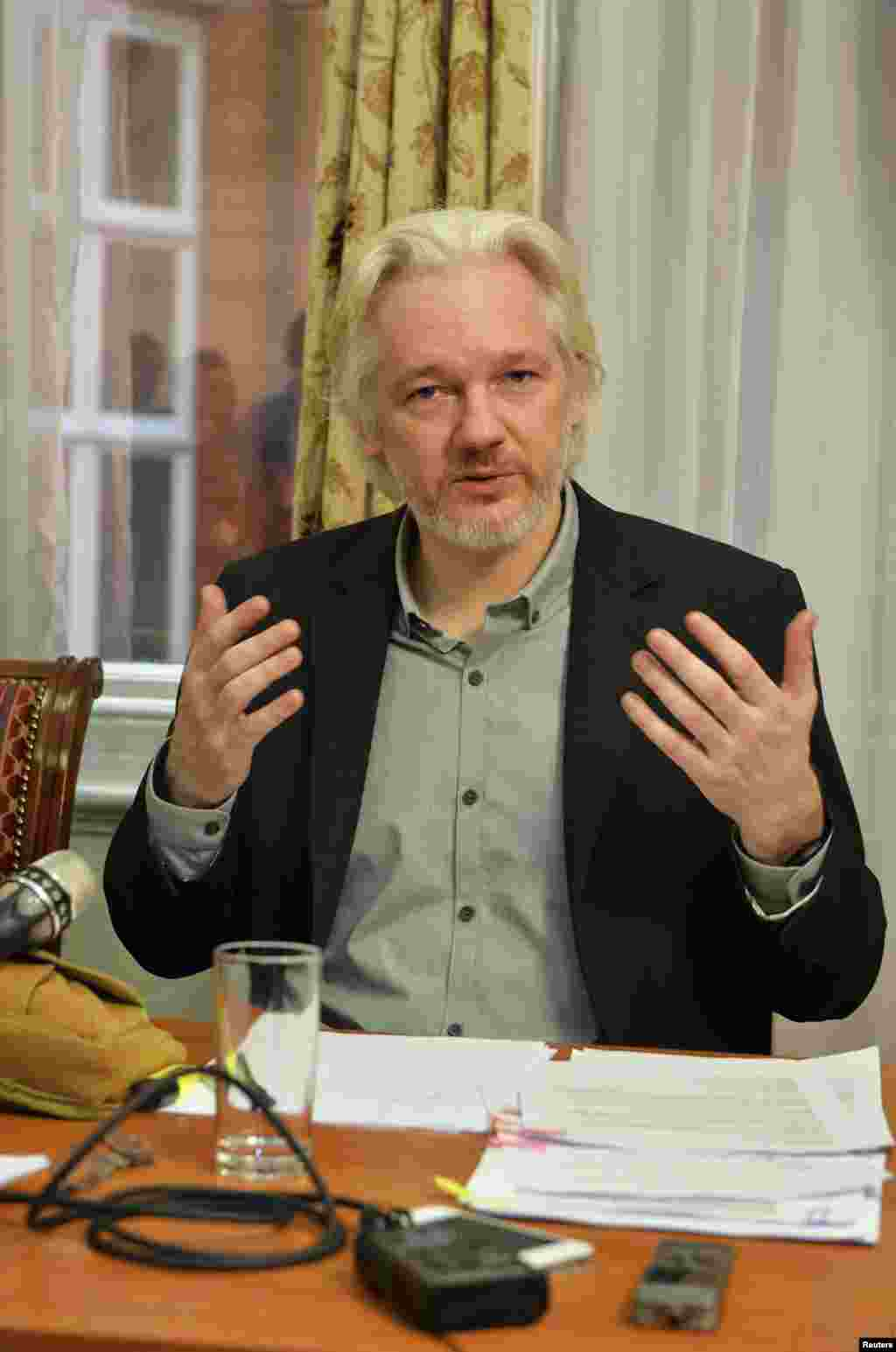 WikiLeaks founder Julian Assange gestures during a news conference at the Ecuadorian embassy, in central London, Aug. 18, 2014.