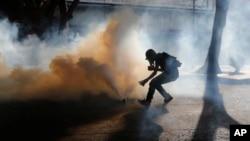 Un manifestante recupera un fraco de gas lacrimógeno lanzado por las fuerzas de seguridad durante una protesta que se dirigía hacia la sede del Consejo Electoral Nacional en Caracas.