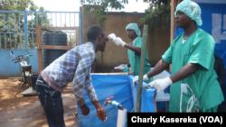 Deux infirmiers à l'entrée d'un centre de traitement de l'épidémie d'Ebola à Beni, 15 octobre 2018. (VOA/Charly kasereka)