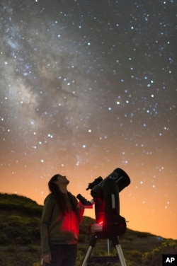 In this image released on Wednesday, July 11, 2018, an Experience guest observes the night sky with a telescope next to the Gran Telescopio Canarias at the Roque de los Muchachos Observatory on the island of La Palma in the Canaries, Spain. (Antoni Clader