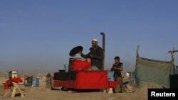 An Afghan man prepares food at his roadside restaurant in Kabul, November 14, 2012.
