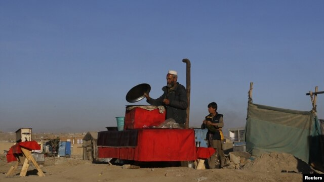 An Afghan man prepares food at his roadside restaurant in Kabul, November 14, 2012.
