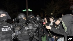 A protester offers police a rose after the deadline passed when the city wanted them to vacate the Occupy Portland Camp in Portland, Oregon, November 13, 2011.