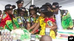 Le président zimbabwéen Robert Mugabe, centre gauche, son épouse Grace, au centre, et des membres de leur famille coupent le gâteau d'anniversaire à Matopos, dans la banlieue de Bulawayo, 25 février 2017.