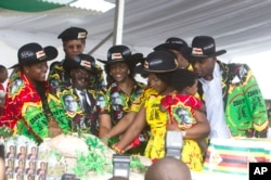 FILE - Zimbabwean President Robert Mugabe, center left, and his wife Grace, center are joined by his family as they cut the cake during his 93rd Birthday celebrations in Matopos on the outskirts of Bulawayo, Feb. 25, 2017.