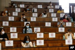 Students sit at a distance as a precaution against COVID-19, as they undergo an aptitude test to access the University of Medicine, in Rome Thursday, Sept. 3, 2020. The faculty of Medicine, as well as other University studies, in Italy require a…