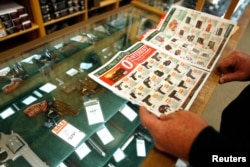 FILE - A customer looks through the in-store sales advertisements inside a store that sells guns in Texas.