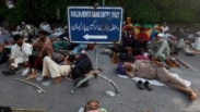 Supporters of Mohammad Tahir ul-Qadri, Sufi cleric and leader of political party Pakistan Awami Tehreek (PAT), sleep at the entrance of the parliament house in Islamabad August 20, 2014. Thousands of protesters marched to the Pakistani parliament on Tuesd