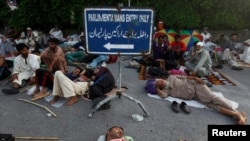 Para pendukung Mohammad Tahir ul-Qadri, ulama sufi dan pemimpin partai Pakistan Awami Tehreek (PAT), tidur-tiduran di gerbang masuk gedung parlemen di Islamabad (20/8).