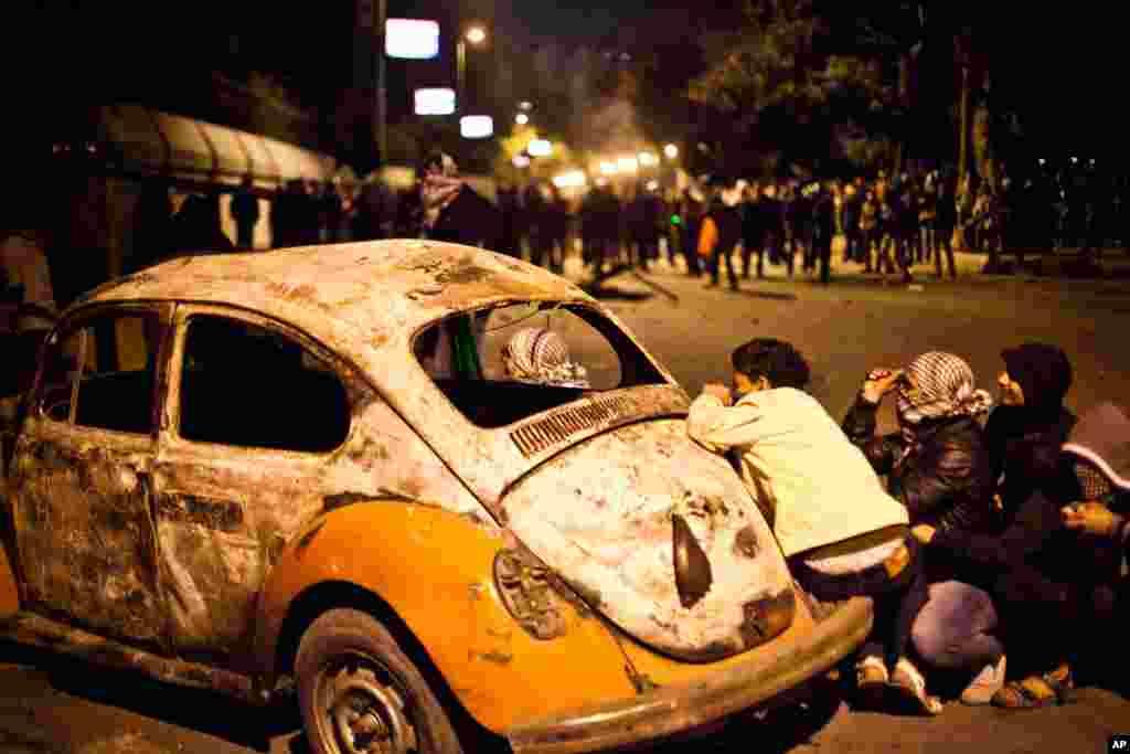 1月28日在埃及的开罗,在与安全部队的冲突中,一名示威者在一辆被损毁的车旁躲避。