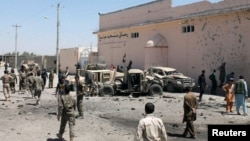 Tentara Nasional Afghanistan (ANA) memeriksa kendaraan militer yang rusak pasca serangan bunuh diri di Lashkar Gah, provinsi Helmand, Afghanistan, 23 Agustus 2017. (REUTERS / Stringer)