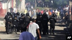 Riot police officers face demonstrators during clashes in La Paz Centro, Leon, Nicaragua, Monday, Nov 5, 2012. The ruling Sandinista Front has won at least 134 of the 153 mayoral races in local elections the opposition and the U.S. government say lacked transparency, according to results released Monday.