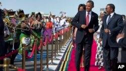 ປະທານາທິບໍດີໂອບາມາ ທີ່ຕິດຕາມດ້ວຍສະຕີໝາຍເລກນຶ່ງ ທ່ານນາງ Michelle ໂອບາມາ ເຕັ້ນເມື່ອທ່ານໄປເຖິງບ່ອນຈັດ ພິທີຕ້ອນຮັບທ່ານ ກັບປະທານາທີບໍດີ Tanzania ທ່ານ Jakaya Kikwete (ຂວາ) ໃນວັນຈັນທີ 1 ກໍລະກົດ 2013 ທີ່ສະໜາມບິນສາກົນ Julius Nyerere ໃນນະຄອນຫລວງ Dar Es Salaam ຂອງ Tanzania.
