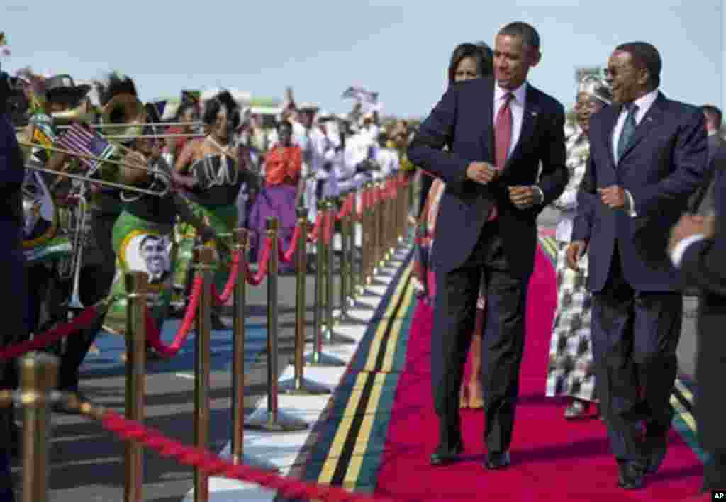 President Barack Obama, followed by first lady Michelle Obama, does a dance upon his arrival ceremony with Tanzanian President Jakaya Kikwete, right, Monday, July 1, 2013, at Julius Nyerere International Airport in Dar Es Salaam, Tanzania. The president i