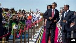 Rais Barack Obama, akifuatiwa na mkewe Michelle Obama, akicheza ngoma na rais wa Tanzania Jakaya Kikwete, right,Jumatatu, July 1, 2013, katika uwanja wa ndege wa kimataifa wa Julius Nyerere Dar Es Salaam, Tanzania.