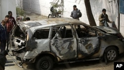 Police officers stand around an Israeli diplomat's car that was damaged in an explosion in New Delhi, India, February 14, 2012.