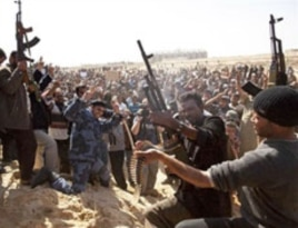 Libyan gunmen from the forces against Libyan leader Moammar Gadhafi fire in the air during a mass funeral for rebel gunmen killed in fighting in Ajdabiya, eastern Libya, March 3, 2011