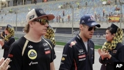 Red Bull driver Sebastian Vettel of Germany, second right, and Lotus driver Kimi Raikkonen of Finland, second left, arrive at the drivers track parade ahead of the Formula One Grand Prix at the Bahrain International Circuit in Sakhir, Bahrain, Sunday, Apr