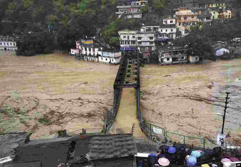 People gather to watch a bridge submerged in the flooded water of the River Ganges in Rudraprayag, in the northern Indian state of Uttarakhand, June 18, 2013.